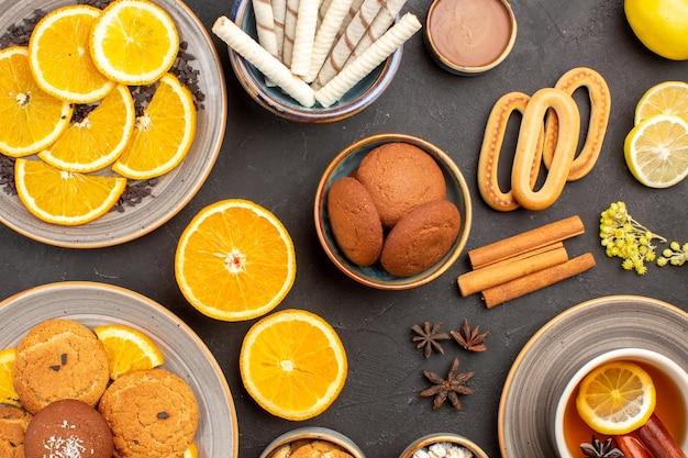 Draufsicht leckere zuckerkekse mit tasse tee und orangen auf dunklem hintergrund zuckertee-fruchtkeksplätzchen süß