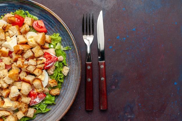 Draufsicht leckeren caesar salat mit geschnittenem gemüse und zwieback innerhalb platte auf der dunklen oberfläche