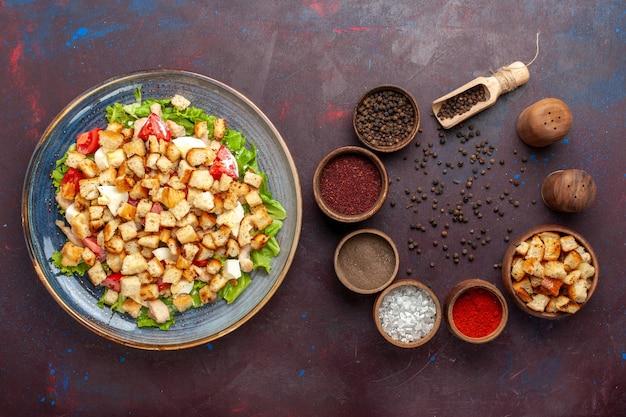 Draufsicht leckeren caesar salat mit gewürzen auf dem dunklen schreibtisch