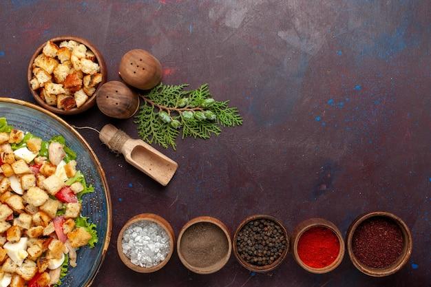 Draufsicht leckeren caesar salat mit verschiedenen gewürzen auf der dunklen oberfläche Kostenlose Fotos