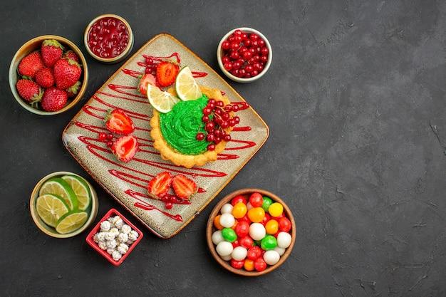 Draufsicht leckeren cremigen kuchen mit erdbeeren auf dunklem boden süßer zuckerdesserttee Kostenlose Fotos