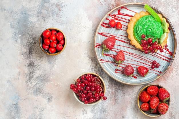 Draufsicht leckeren cremigen kuchen mit frischen früchten auf dem hellen tischkeksdessertkuchen süß