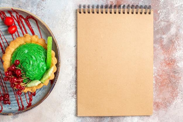Draufsicht leckeren cremigen kuchen mit früchten auf leichtem tischkeksdessert-süßigkeitskuchen
