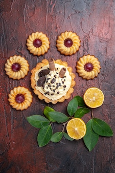 Draufsicht leckeren cremigen kuchen mit keksen auf dem dunklen tischdessert süßer kekskuchen