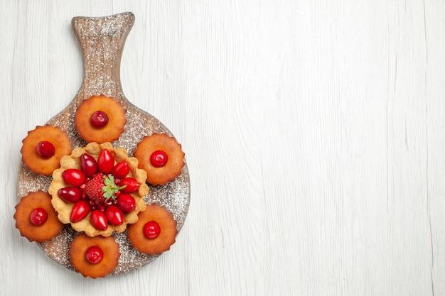 Draufsicht leckeren cremigen kuchen mit kuchen und früchten auf einem hellen weißen schreibtisch