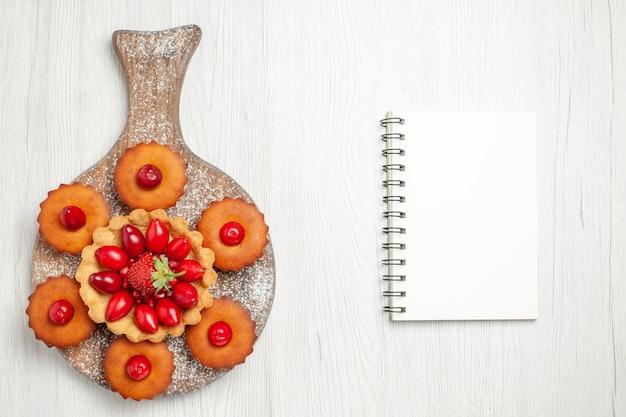Draufsicht leckeren cremigen kuchen mit kuchen und früchten auf weißem schreibtisch