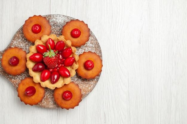 Draufsicht leckeren cremigen kuchen mit kuchen und früchten auf weißem schreibtisch Kostenlose Fotos