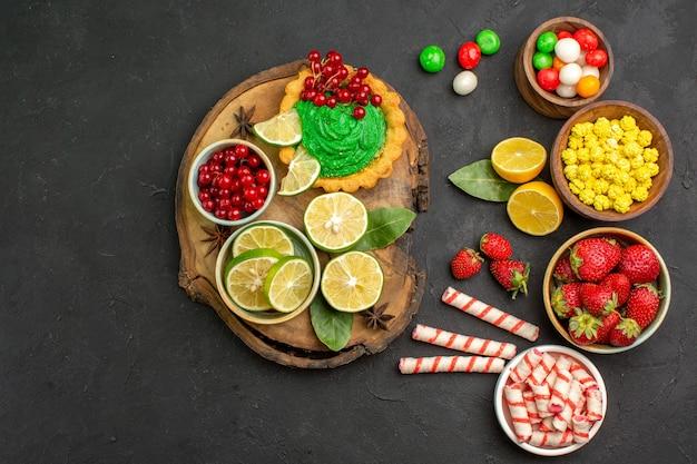 Draufsicht leckeren cremigen kuchen mit süßigkeiten und früchten auf dunklem schreibtisch süßer kekskeks