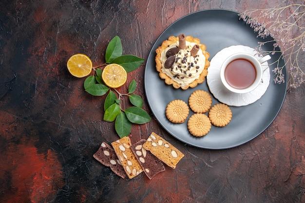 Draufsicht leckeren cremigen kuchen mit tasse tee auf dunklem tischkuchen süßes dessert