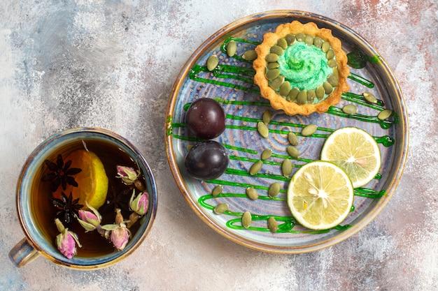 Draufsicht leckeren cremigen kuchen mit tasse tee auf hellem hintergrund süßer bonbonkeks
