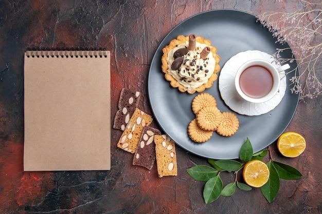 Draufsicht leckeren cremigen kuchen mit tee und keksen auf dem dunklen tisch süßer kuchen nachtisch