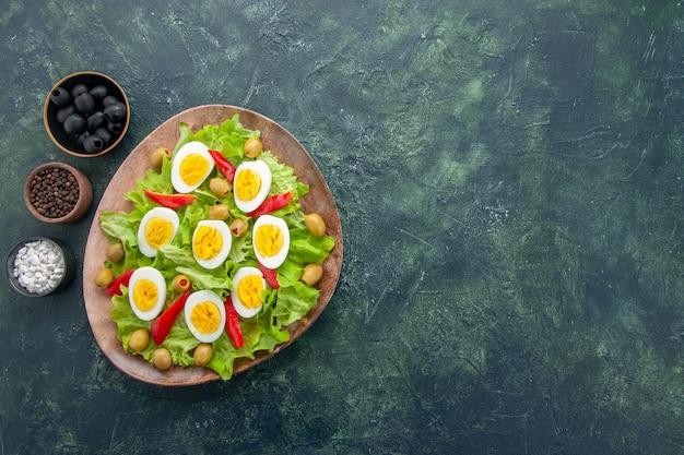 Draufsicht leckeren eiersalat mit grünen salatoliven und gewürzen auf dunkelblauem hintergrund