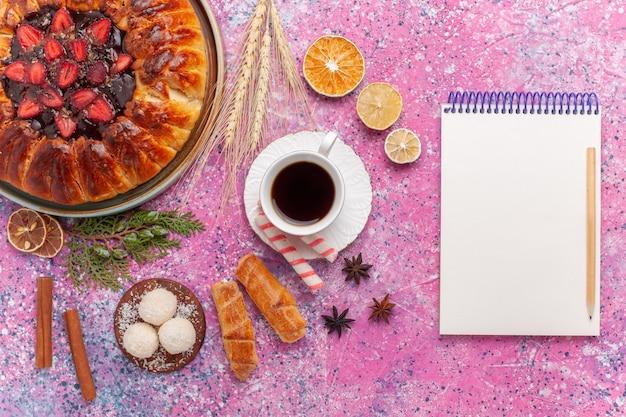 Draufsicht leckeren erdbeerkuchen fruchtigen kuchen mit tasse tee auf dem rosa
