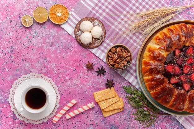 Draufsicht leckeren erdbeerkuchen fruchtigen kuchen mit tee auf rosa
