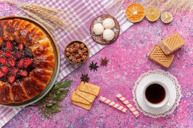 Draufsicht leckeren erdbeerkuchen fruchtigen kuchen mit tee und waffeln auf rosa