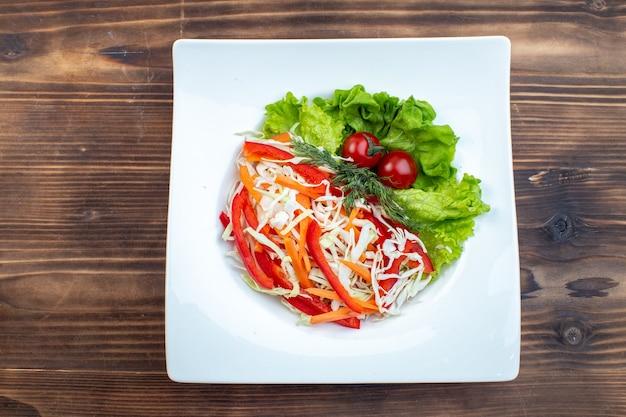 Draufsicht leckeren gemüsesalat mit grünem salat und kohl innerhalb platte auf brauner oberfläche
