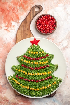 Draufsicht leckeren grünen salat in der neujahrsbaumform innerhalb platte auf hellem hintergrund