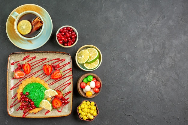 Draufsicht leckeren kuchen mit früchten und tee auf grauem hintergrundplätzchenkeks süß