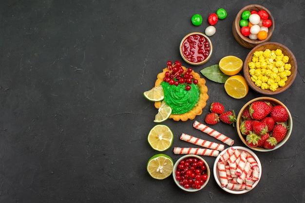 Draufsicht leckeren kuchen mit süßigkeiten und früchten auf dunklem hintergrund kekskeks süßer freier platz
