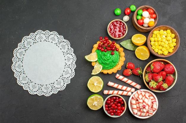 Draufsicht leckeren kuchen mit süßigkeiten und früchten auf dunklem schreibtischplätzchenkeks süß