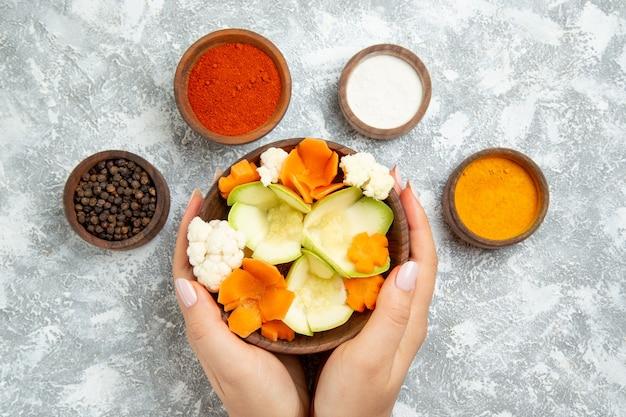 Draufsicht leckeren nützlichen salat mit gewürzen auf weißem hintergrund salatgemüse mahlzeit lebensmittelgesundheit