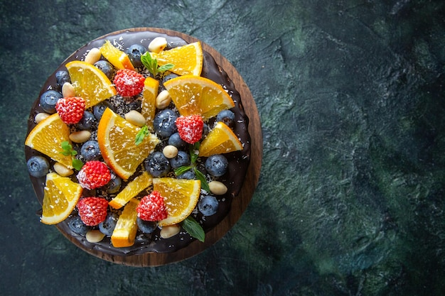 Draufsicht leckeren schokoladenkuchen mit frischen früchten auf dunkelheit