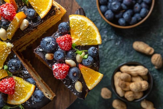 Draufsicht leckeren schokoladenkuchen mit früchten auf dunkelheit