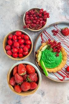 Draufsicht leckerer cremiger kuchen mit frischen früchten auf einem leichten tischkeks süßer dessertkuchen