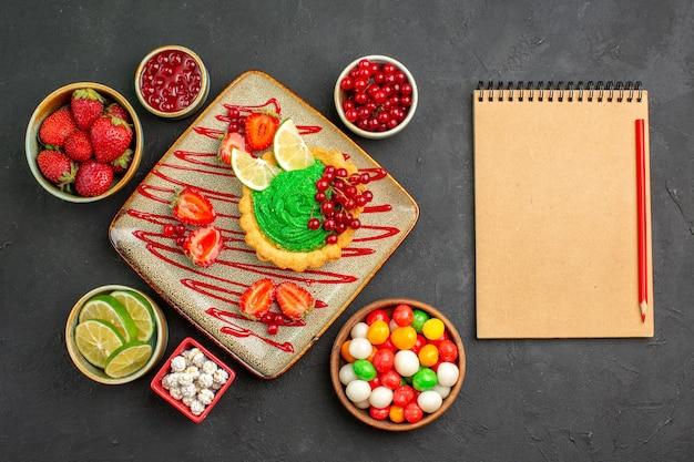 Draufsicht leckerer cremiger kuchen mit früchten auf dunklem hintergrundkeksdessert süß