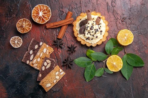 Draufsicht leckerer cremiger kuchen mit kuchen auf dunklem tischdessert süßer kekskuchen