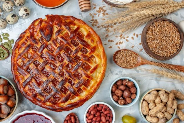 Draufsicht leckerer fruchtiger kuchen mit nüssen und eiern auf hell gebackenem kekskuchen dessertkuchen keks bäckerei brötchen farbe