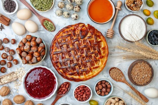 Draufsicht leckerer fruchtiger kuchen mit nüssen und eiern auf leicht gebackenem kekskuchen dessert tee kuchen keks bäckerei brötchen