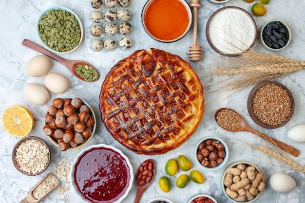 Draufsicht leckerer fruchtiger kuchen mit nüssen und eiern auf leicht gebackenem kekskuchen dessertfarbe teekuchen keks bäckerei brötchen