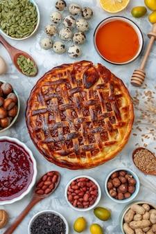 Draufsicht leckerer fruchtiger kuchen mit nüssen und eiern auf leicht gebackenem kekskuchen dessertfarbe teekuchen keksbrötchen