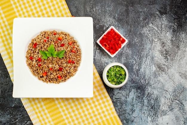 Draufsicht leckerer gekochter buchweizen in weißer platte mit grüns auf hellgrauer tischfarbe