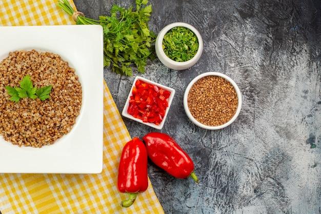 Draufsicht leckerer gekochter buchweizen mit frischem grün und paprika auf hellgrauem tisch
