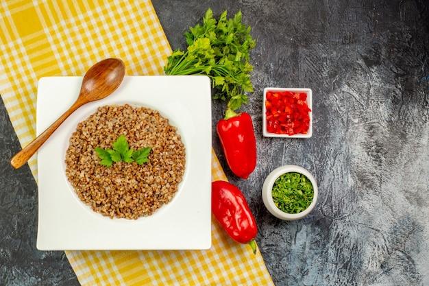 Draufsicht leckerer gekochter buchweizen mit gemüse und paprika auf dem hellgrauen tisch