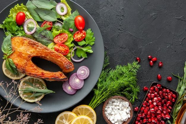 Draufsicht leckerer gekochter fisch mit frischem gemüse auf einem dunklen tisch meeresfrüchtefarbe lebensmittelgericht foto fleisch