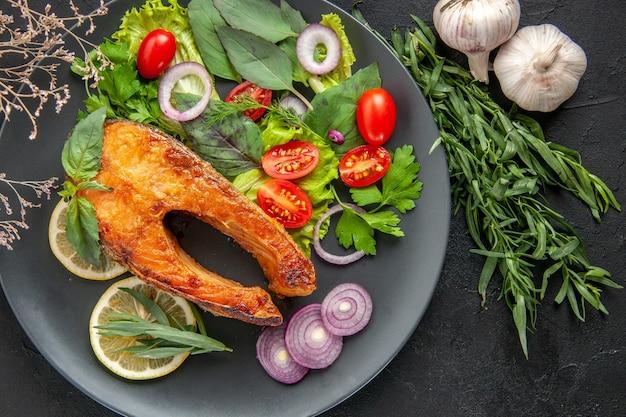 Draufsicht leckerer gekochter fisch mit frischem gemüse und gewürzen auf dem dunklen tisch