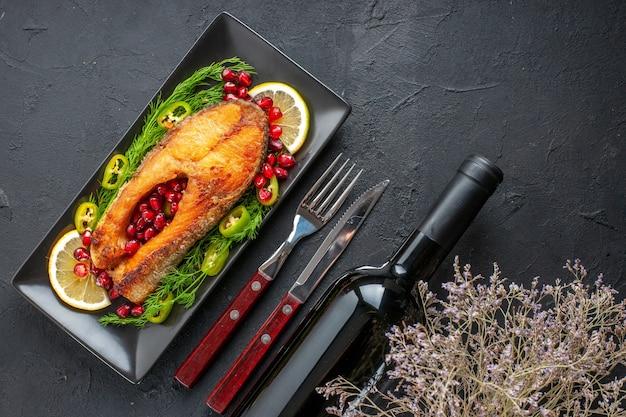 Draufsicht leckerer gekochter fisch mit gemüse und zitronenscheiben in der pfanne auf dunklem tisch