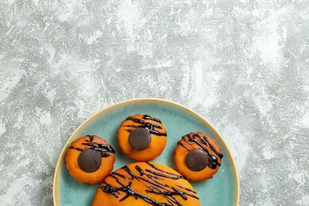Draufsicht leckerer kakaokuchen mit schokoladenglasur im inneren des tellers auf weißer oberfläche süßer kuchen keks dessert cookie pie