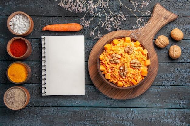 Draufsicht leckerer karottensalat mit walnüssen und gewürzen auf dunkelblauem schreibtisch nusssalat farbe gesundheitsdiät
