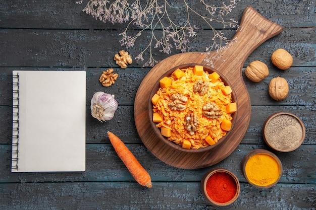 Draufsicht leckerer karottensalat mit walnüssen und gewürzen auf dunkelblauem schreibtisch nusssalat gesundheit diät farbnahrung