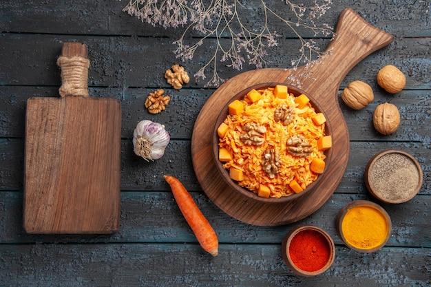 Draufsicht leckerer karottensalat mit walnüssen und gewürzen auf dunkelblauem schreibtischsalat nussgesundheitskost