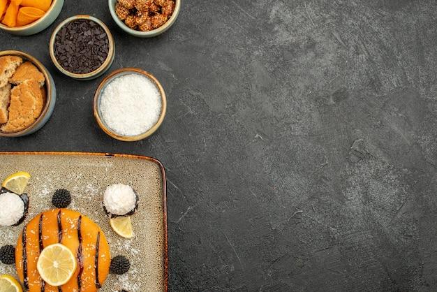 Draufsicht leckerer kleiner kuchen mit kokosbonbons auf dem dunklen schreibtisch kuchen dessertkuchen keks teesüßigkeit