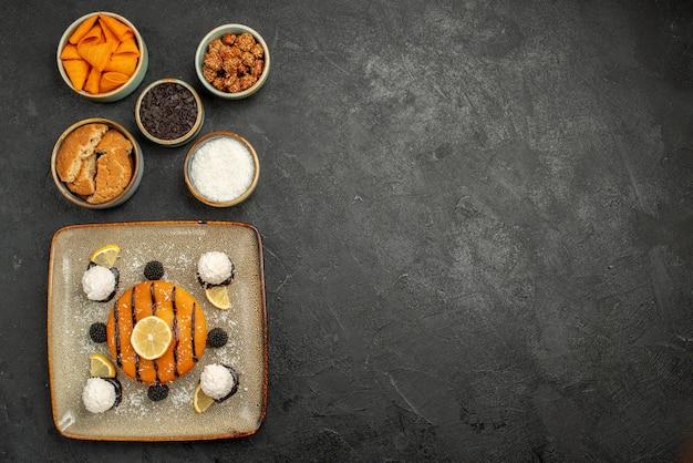 Draufsicht leckerer kleiner kuchen mit kokosbonbons auf dunkler oberfläche kuchenplätzchen-dessertkuchen-keks-tee-süßigkeit