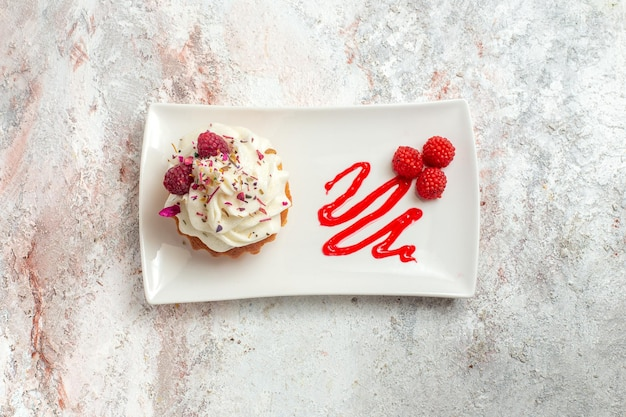 Draufsicht leckerer kleiner kuchen mit sahne und himbeeren auf weißem hintergrund teekuchen keks süße sahne dessert