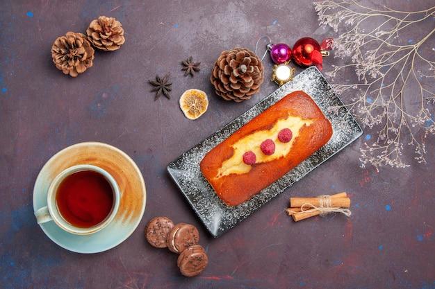 Draufsicht leckerer kuchen, lang mit einer tasse tee auf dunklem oberflächenkuchen, zuckerplätzchenkuchen, süßer kekstee, geformt