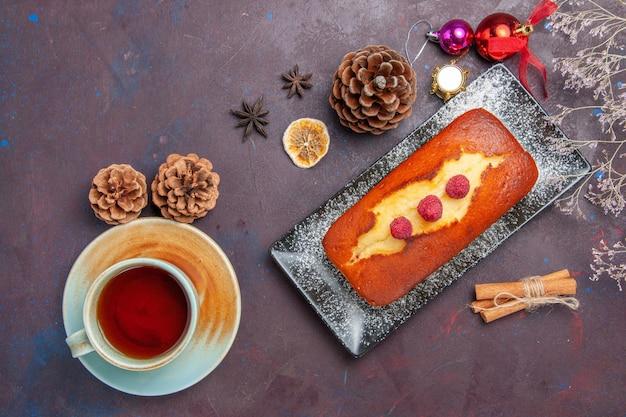 Draufsicht leckerer kuchen, lang mit tee auf dunklem oberflächenkuchen, zuckerplätzchenkuchen, süßer kekstee, geformt