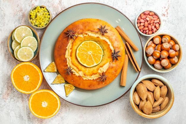 Draufsicht leckerer kuchen mit nüssen und frischen zitrusfrüchten auf weißem hintergrund obst süßer nusskuchen kuchen keks